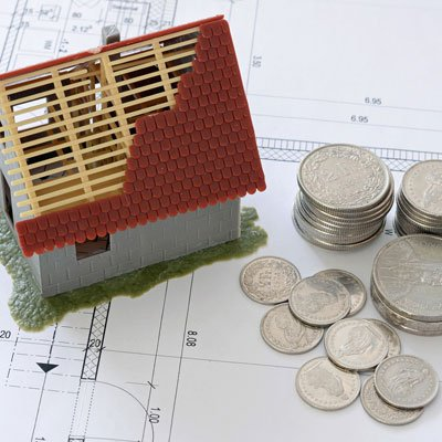 Model of house on top of plans and by a pile of money